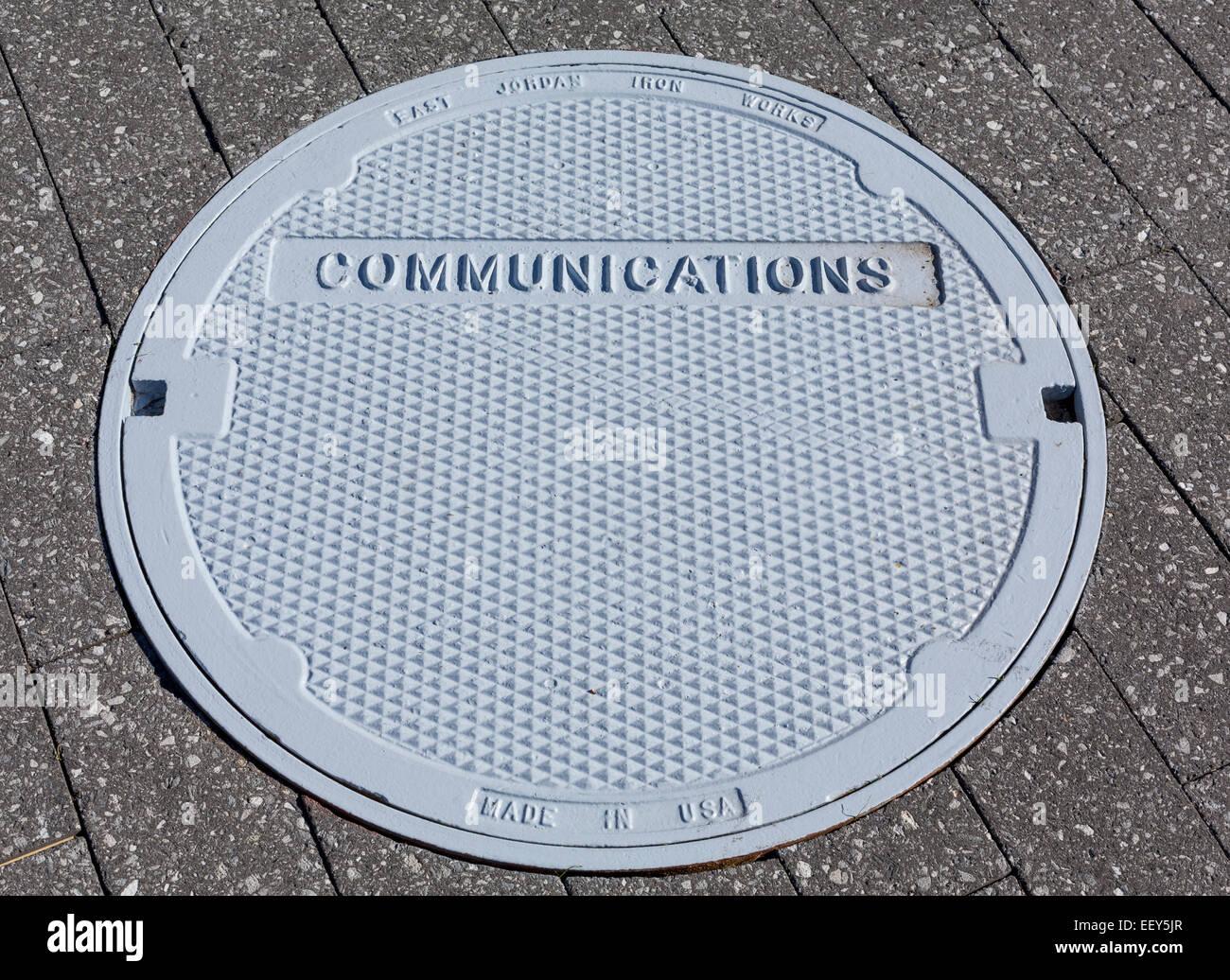 Tapa de registro de comunicaciones en un pavimento - concepto de comunicación Imagen De Stock