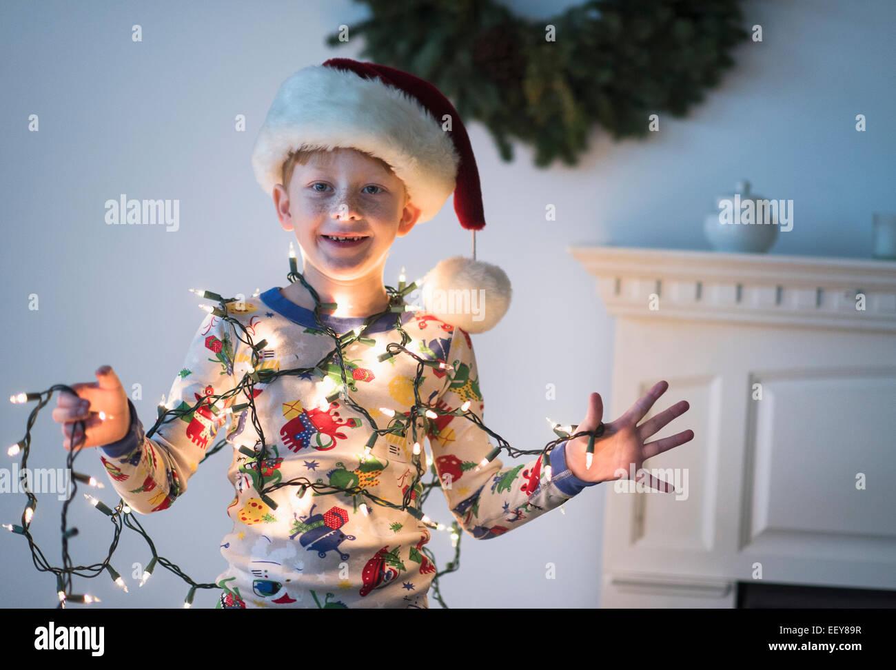 Retrato de niño (6-7) que sujetan las luces de Navidad Imagen De Stock