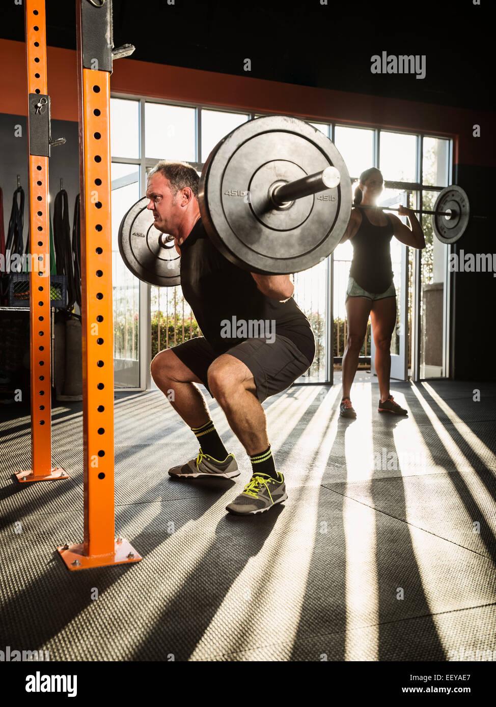 El hombre y la mujer haciendo ejercicio en el gimnasio Imagen De Stock