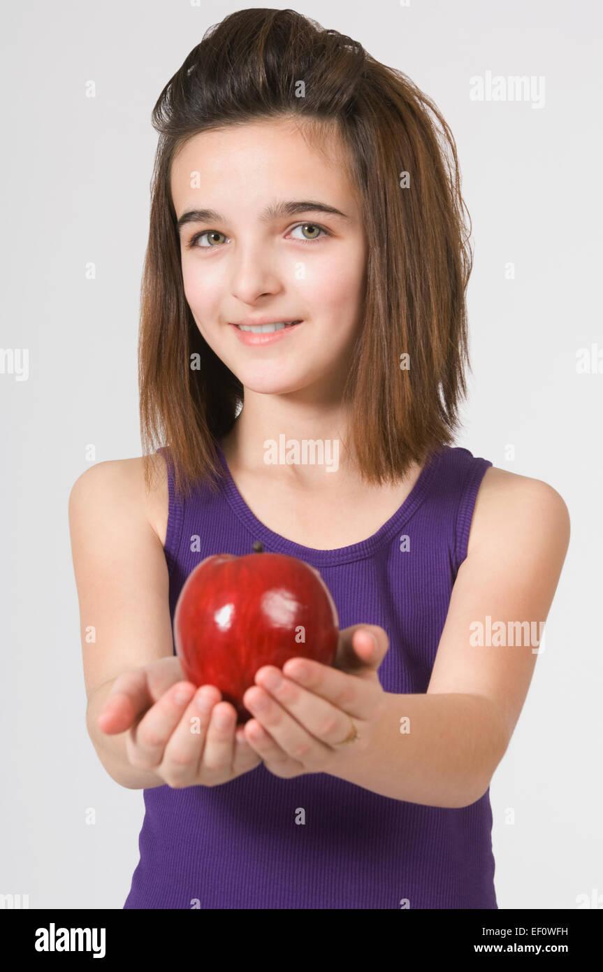 Joven Chica sujetando una manzana Foto de stock