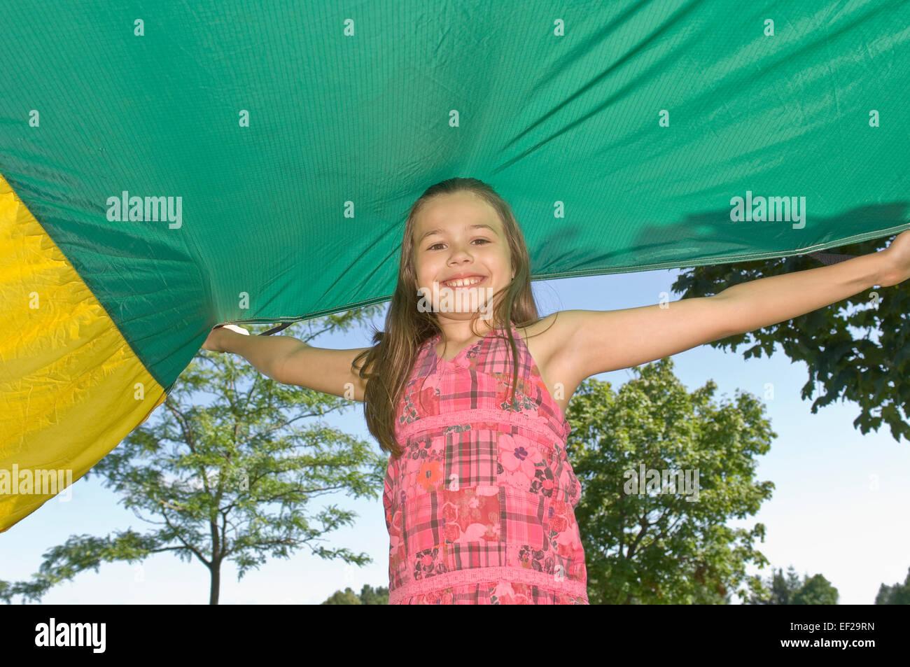 Chica pararse bajo un paracaídas Foto de stock