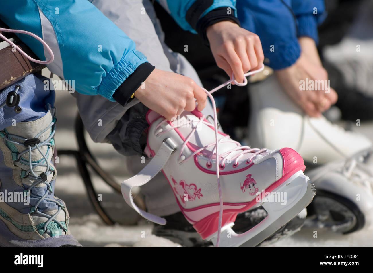 Niña con lazos de patines en el exterior Foto de stock