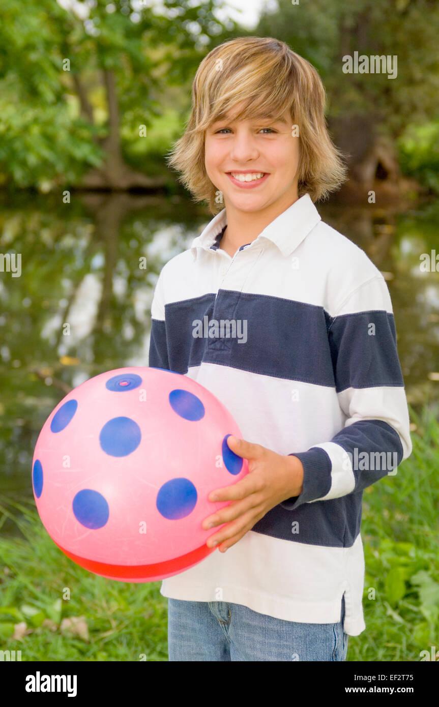 Joven sosteniendo un balón de playa Foto de stock