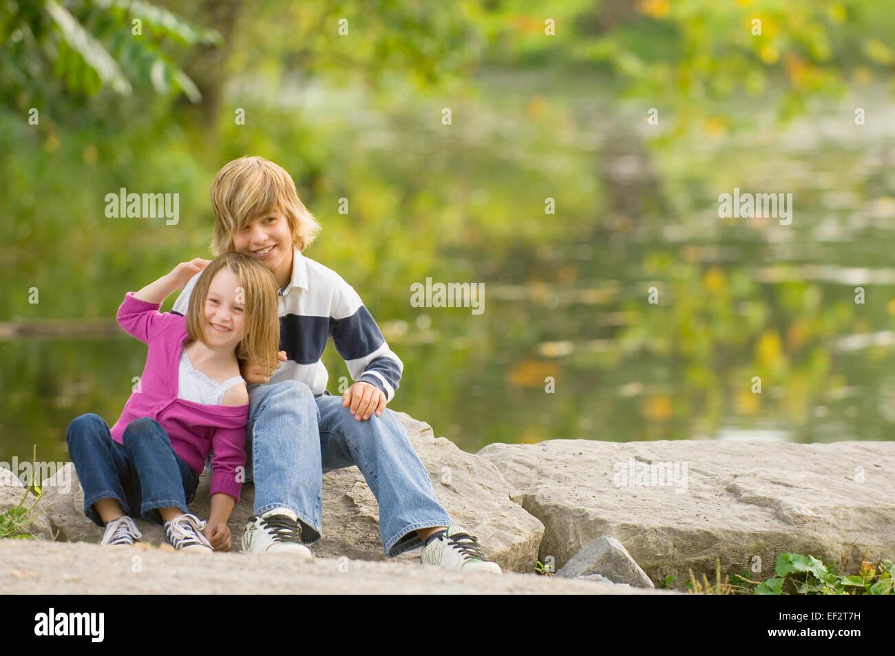 Hermanos sentado sobre una roca por el borde del estanque Foto de stock