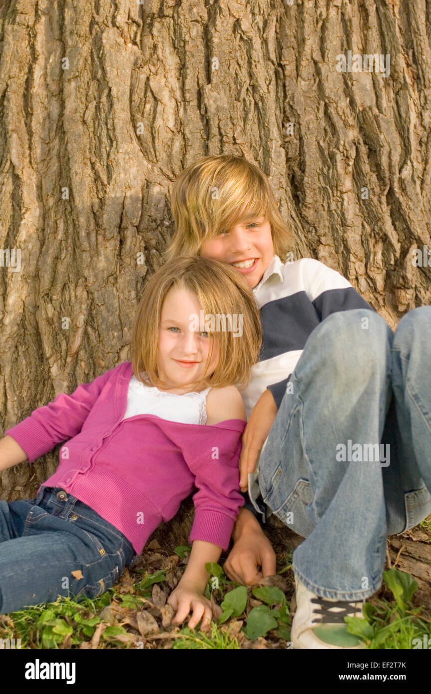 Hermanos inclinada contra un gran tronco de árbol Foto de stock
