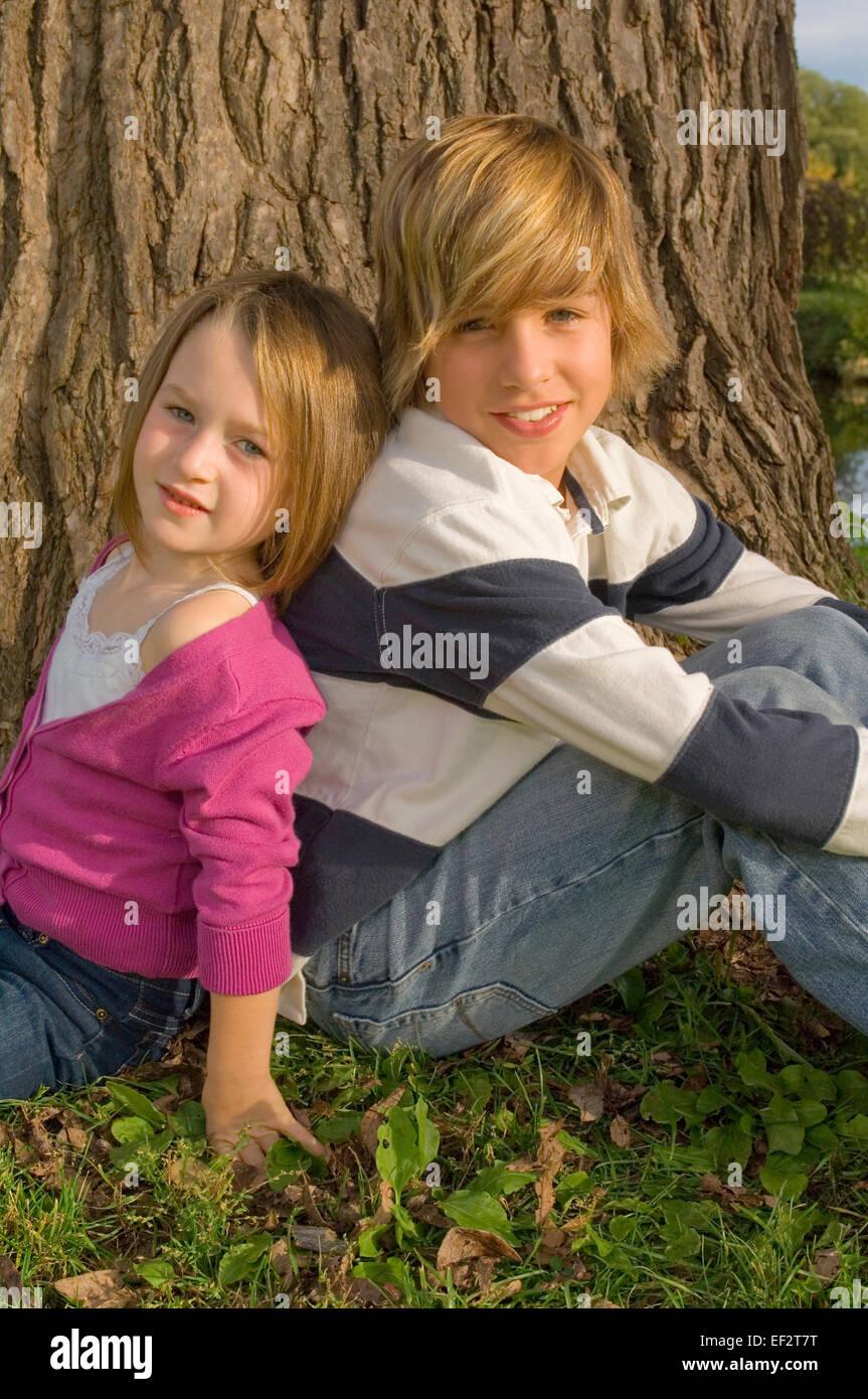 Hermanos sentados espalda con espalda en la parte delantera del árbol grande Foto de stock