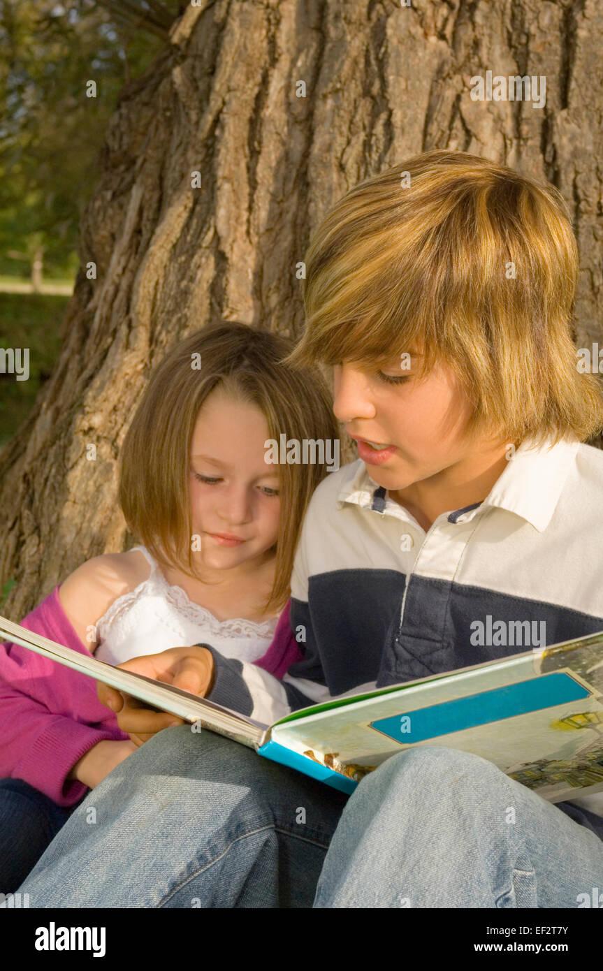 Hermano libro de lectura para Little Sister en estacionamiento Foto de stock