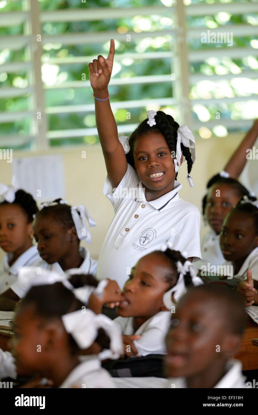 Colegiala levantando su mano en clase, la clase de la Escuela Primaria Basile Moreau, Carrefour, Port-au-Prince, Imagen De Stock