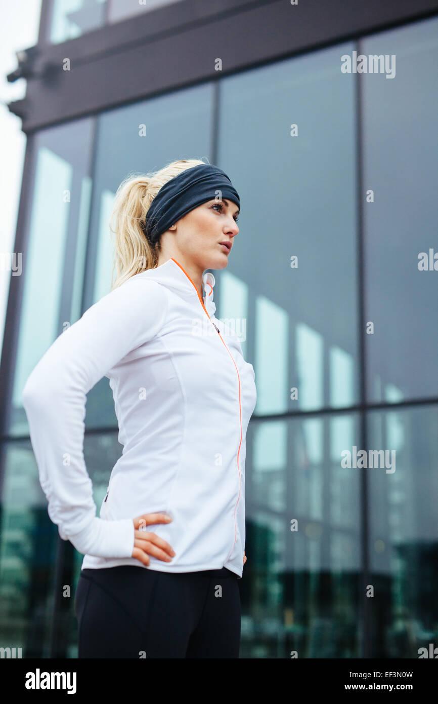 Foto de un atractivo joven listo para su sesión en ejecución. La atleta femenina de gimnasia de pie afuera, Imagen De Stock