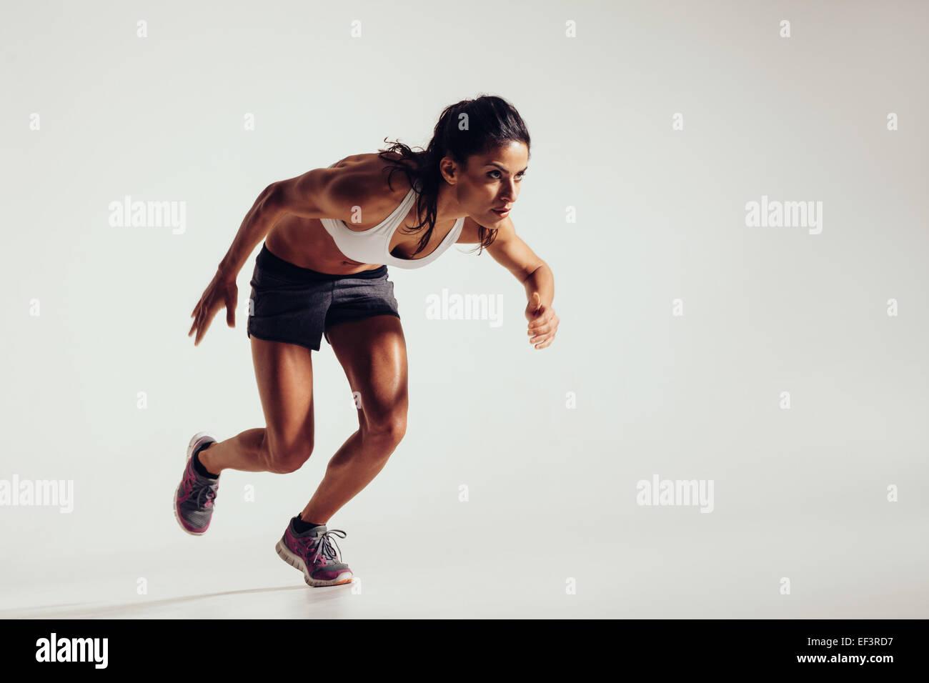 Energética mujer joven corriendo sobre fondo gris. Centrado joven atleta femenina en ejecución. Imagen De Stock