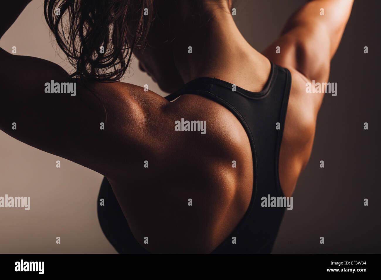 Primer plano de la parte posterior del modelo de fitness femenino. Joven en ropa deportiva con cuerpo musculoso. Imagen De Stock