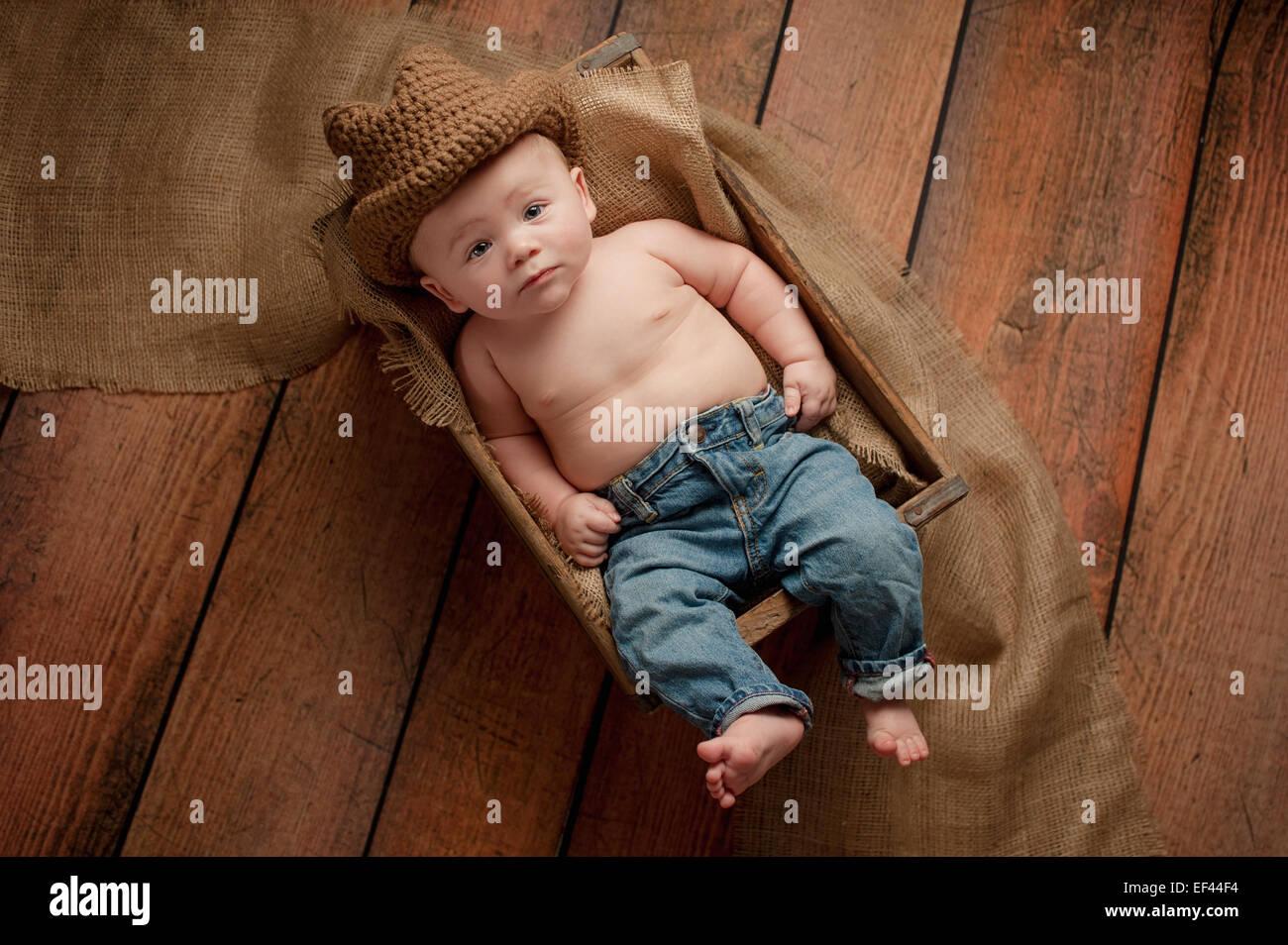 06c7daaa0 Un bebé de 4 meses niño usando un sombrero de vaquero de ganchillo. Él está  mintiendo en una caja de madera forrada con arpillera. Filmado en el estudio