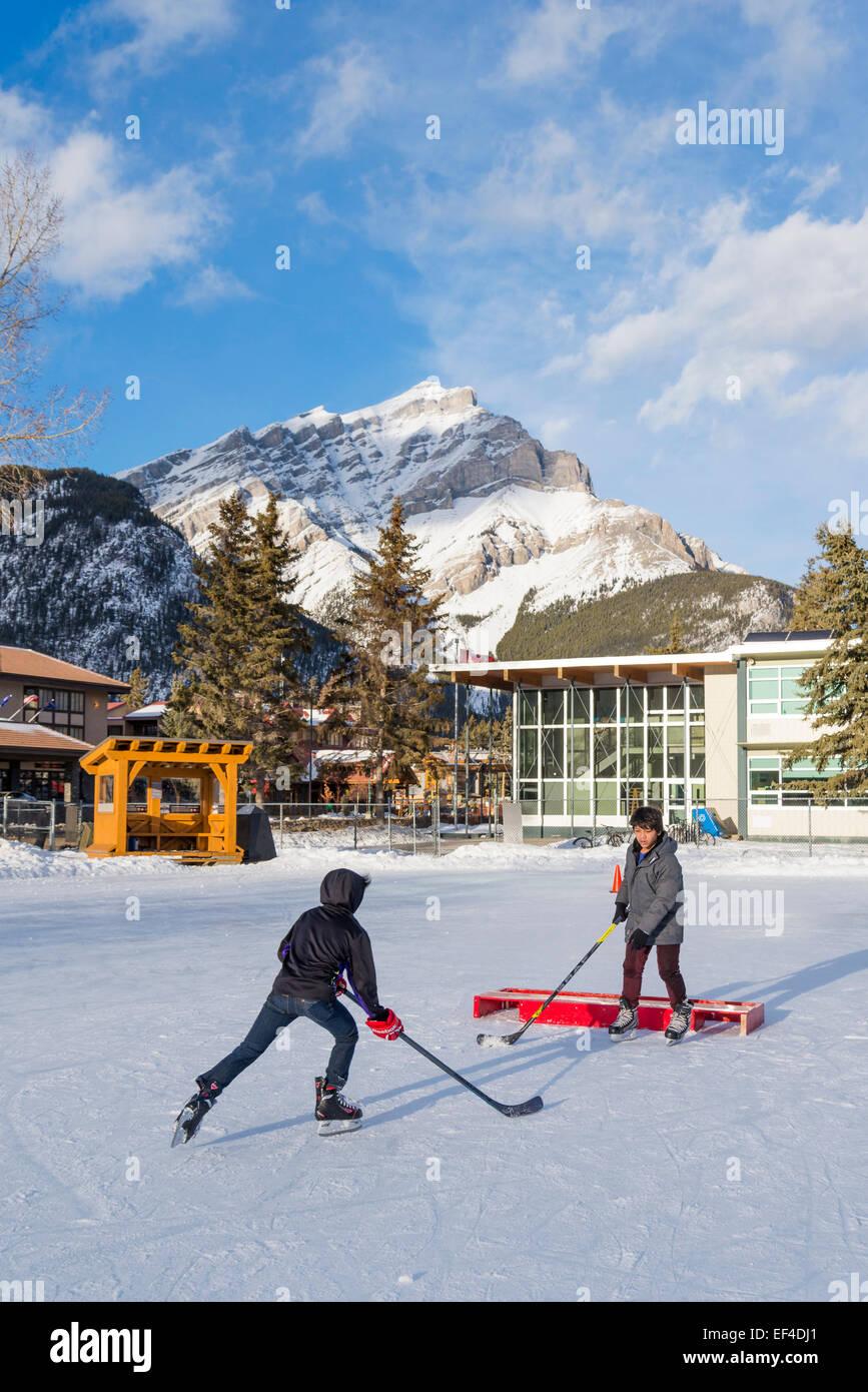 Niños jugando hockey sobre hielo, de Banff, el Parque Nacional de Banff, Alberta, Canadá Imagen De Stock