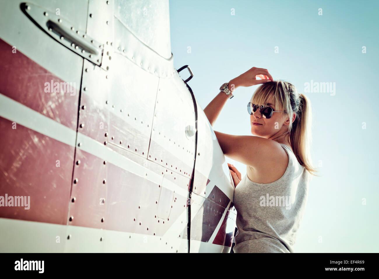 Mujer joven RECOSTADA contra el avión de hélice Imagen De Stock