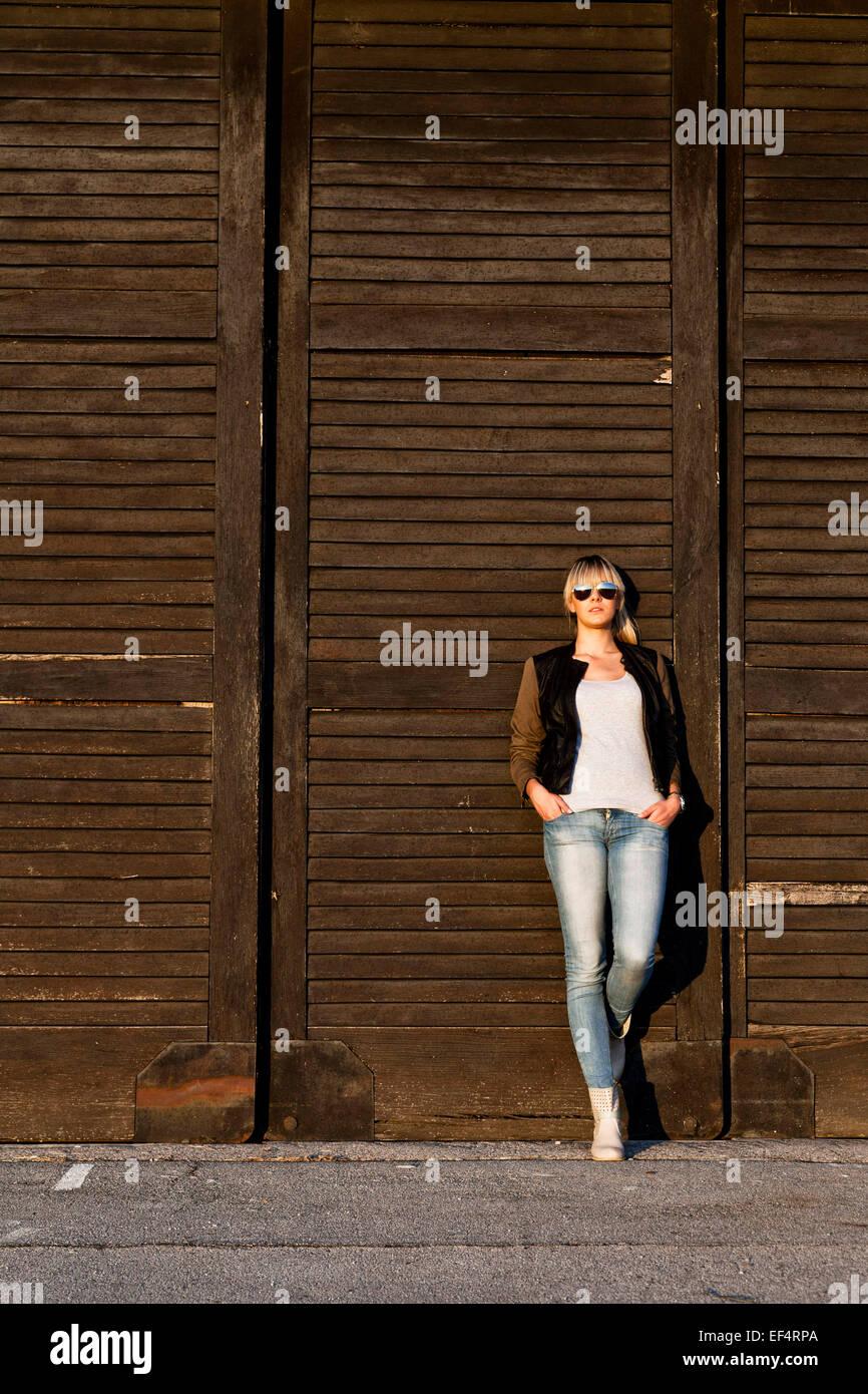 Mujer joven con gafas de sol recostado contra la puerta de madera Imagen De Stock