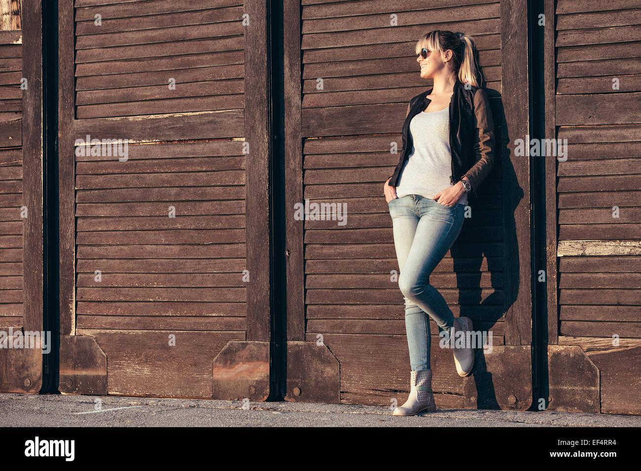 Retrato de mujer joven con gafas de sol contra la puerta de madera Imagen De Stock