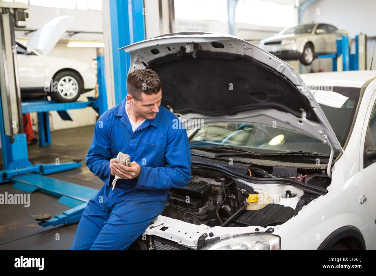 Mecánico sonriendo mirando coche Imagen De Stock