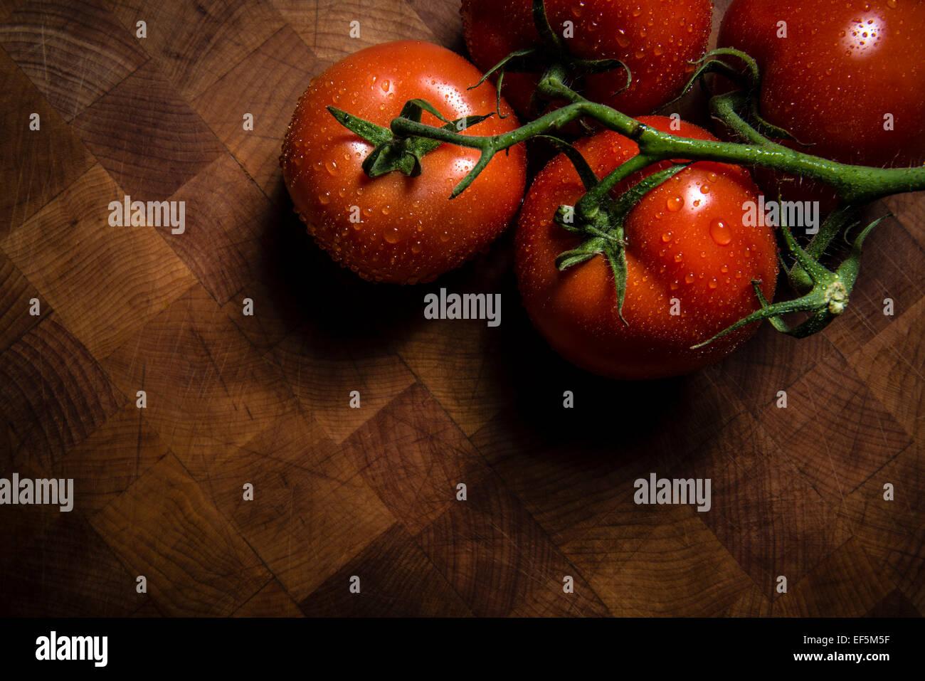 Tomates húmedo sobre una tabla de cortar Imagen De Stock