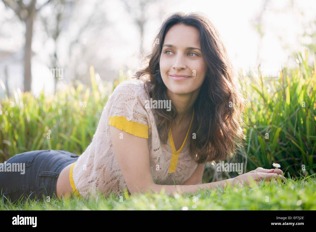 Feliz hermosa mujer recostada sobre la hierba Imagen De Stock