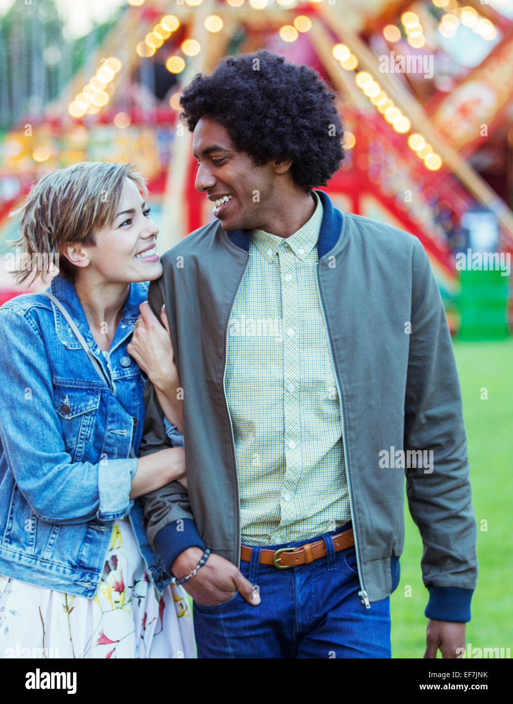 Joven pareja multirracial sonriendo el uno al otro en el parque de diversiones Foto de stock