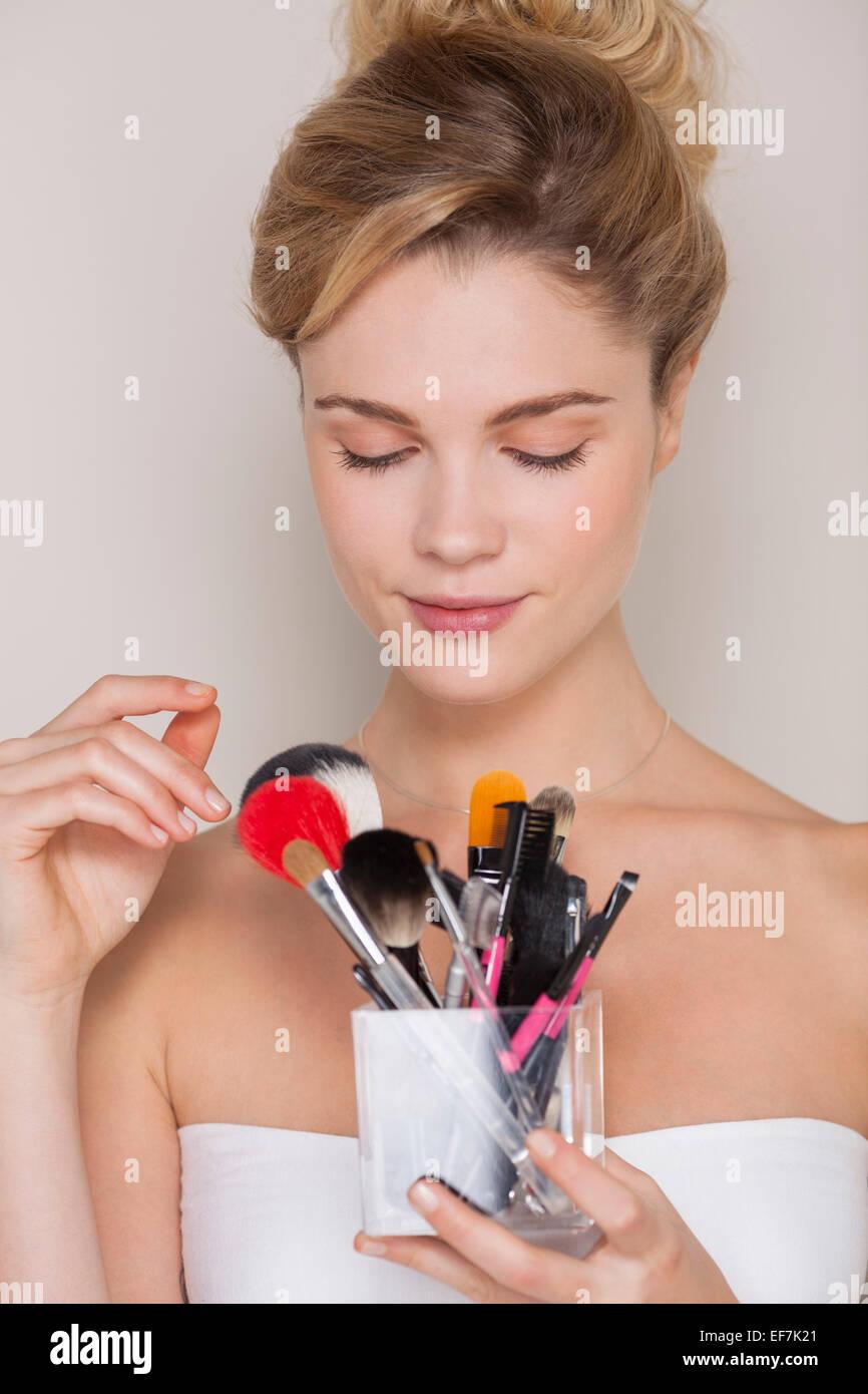 Hermosa mujer sosteniendo surtido de brochas de maquillaje Imagen De Stock