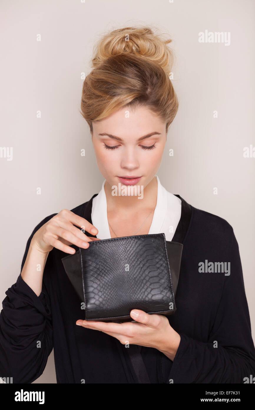 Bella mujer revisando su bolsa para maquillaje Imagen De Stock