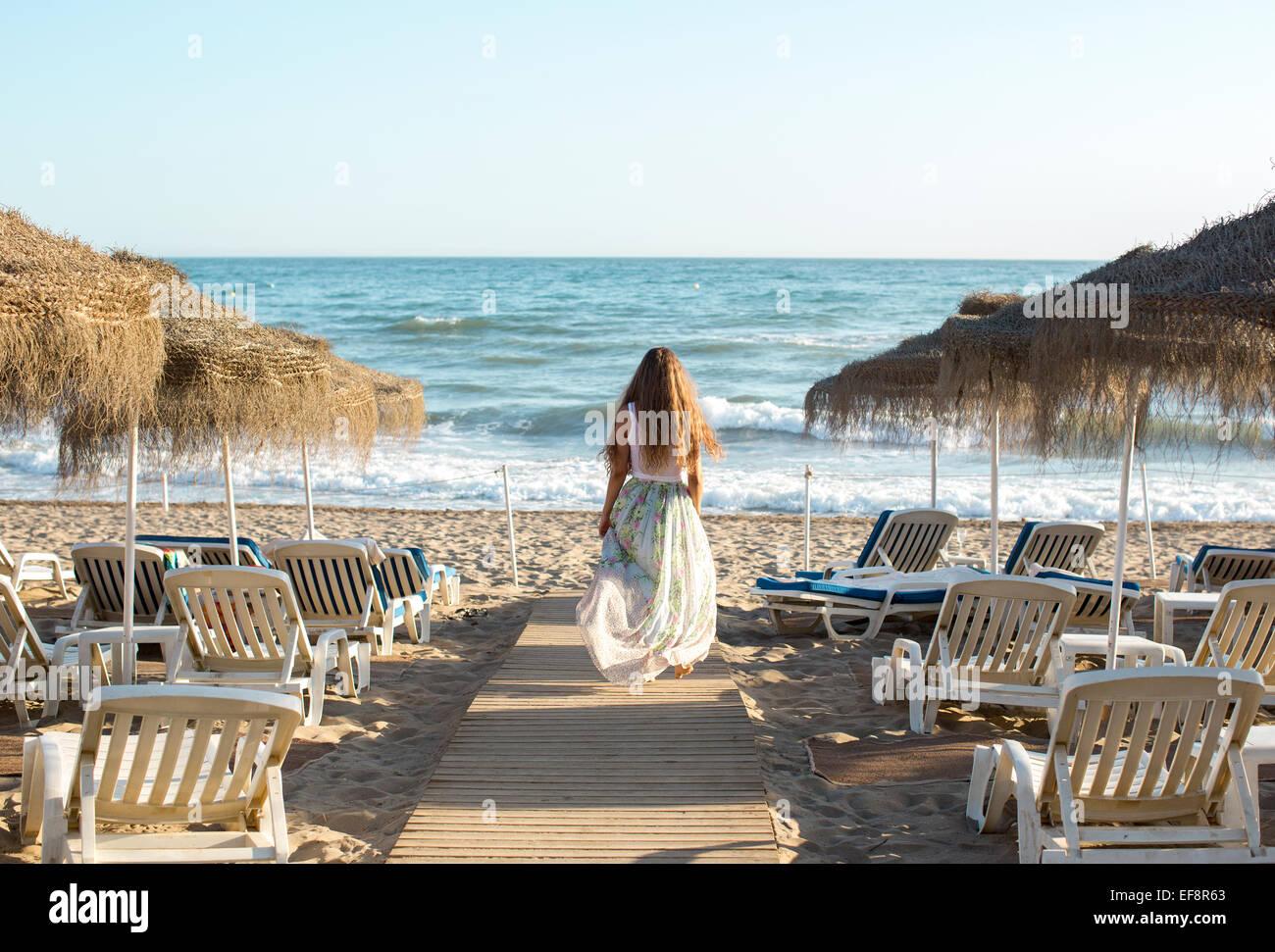 Vista trasera de la joven mujer rubia caminando hacia la playa Imagen De Stock