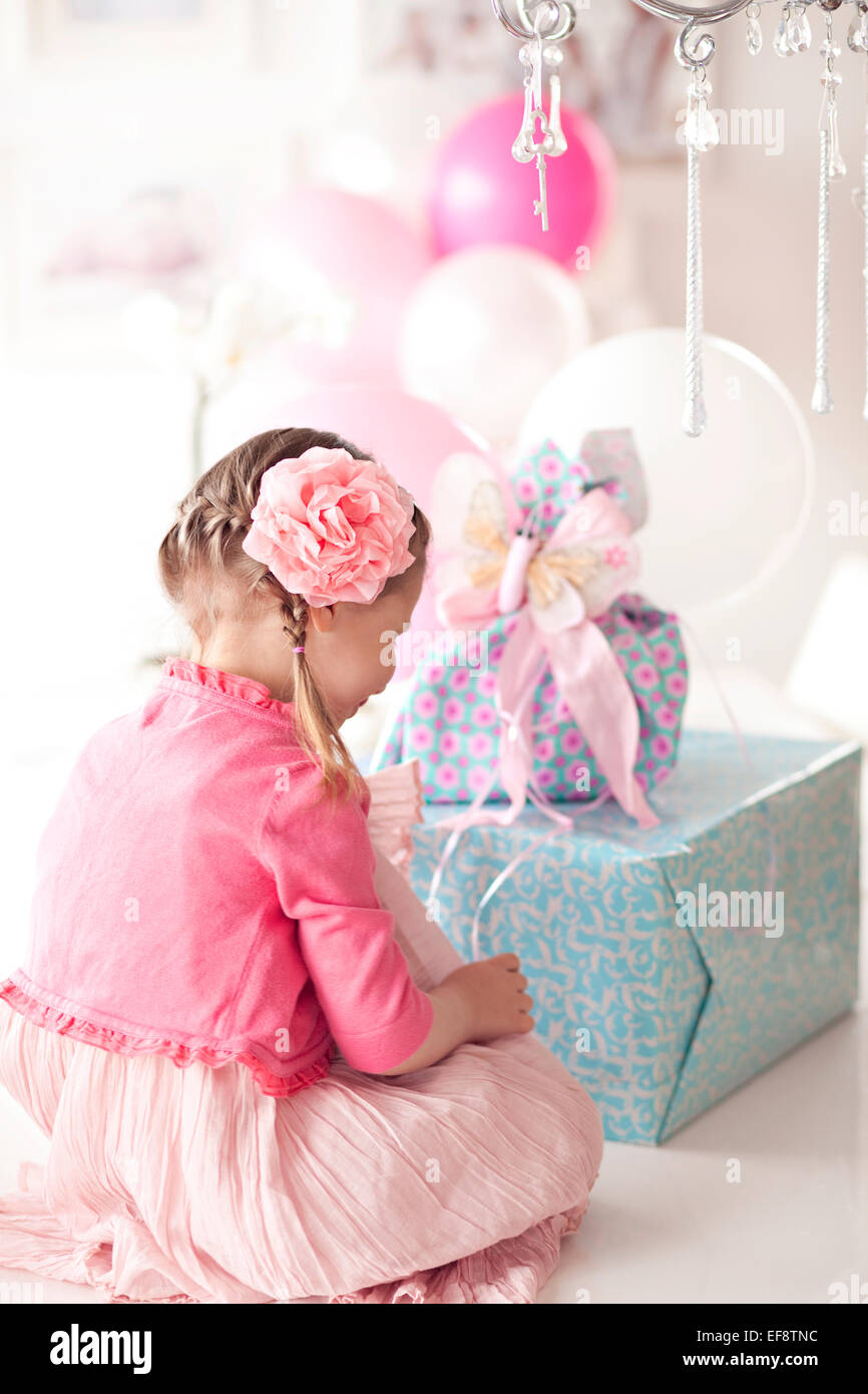 Chica sentada frente a una pila de regalos de cumpleaños Foto de stock