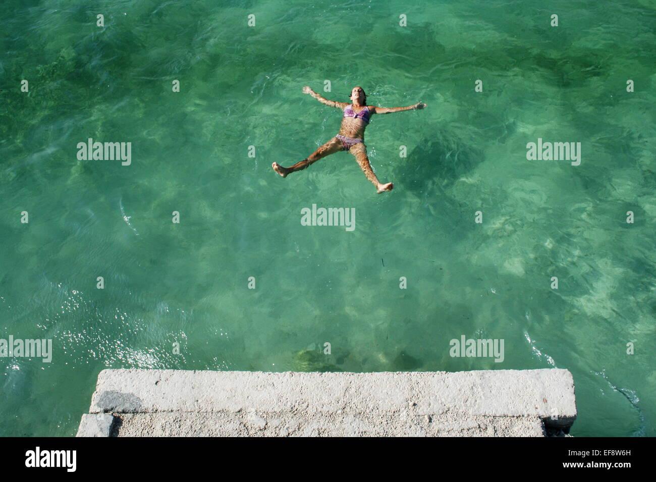 Croacia, Dalmacia, Trogir, Mid-mujer adulta flotando en el mar verde Imagen De Stock