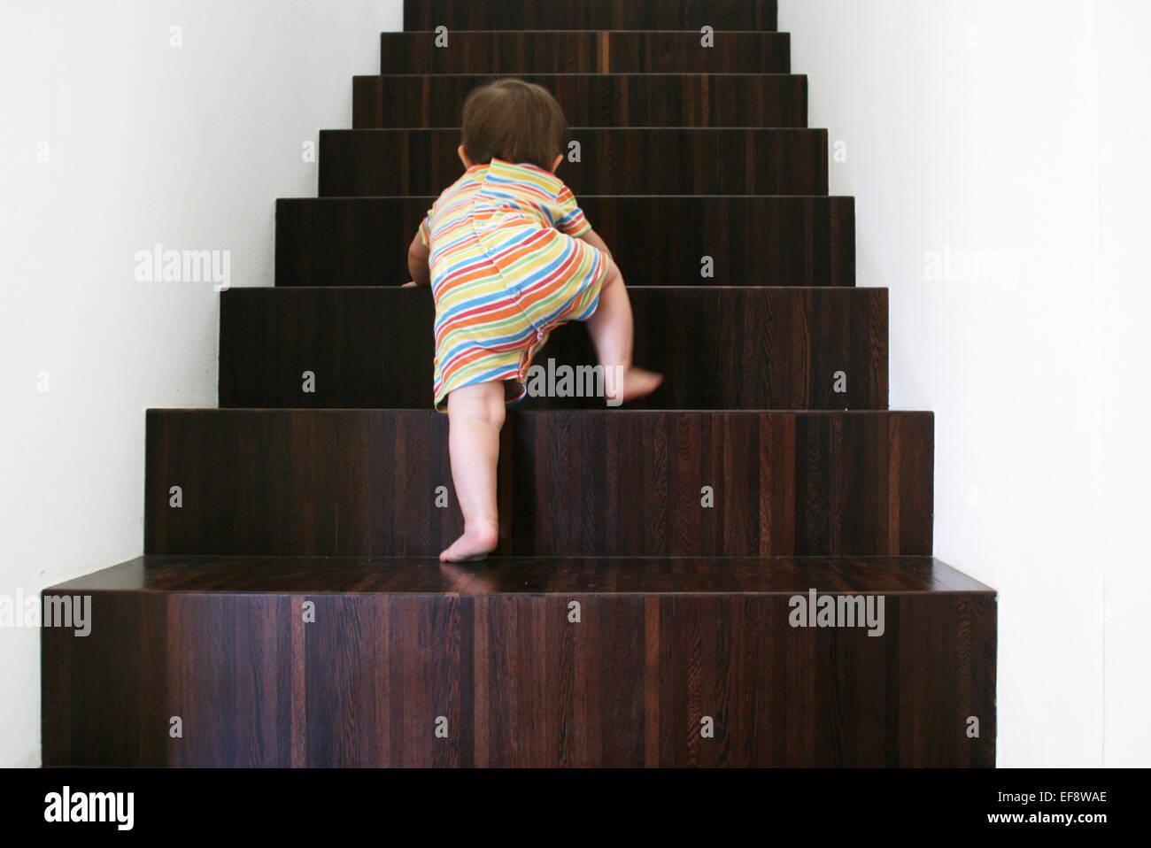 Bebé subiendo escaleras de madera Imagen De Stock