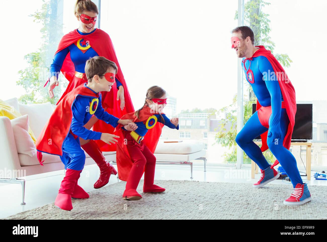La familia de superhéroes persiguiendo unos a otros en la sala de estar Foto de stock