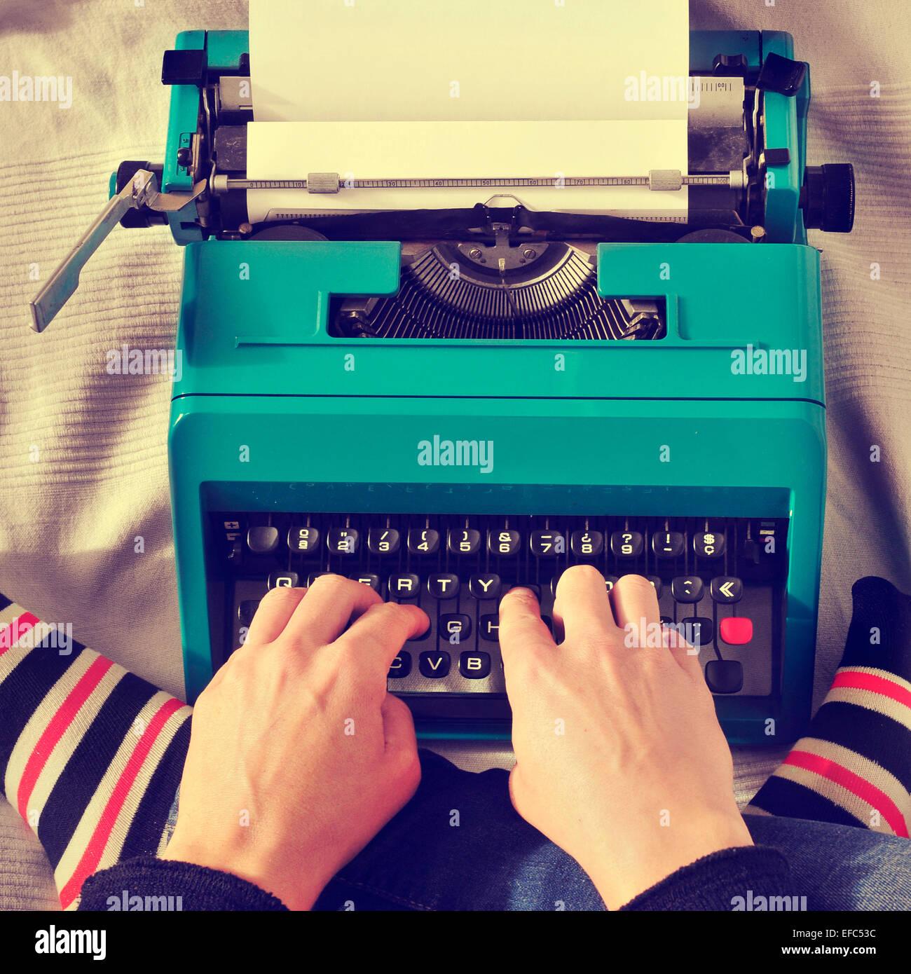 Un hombre joven escribiendo en una vieja máquina en la cama, con un efecto retro Foto de stock