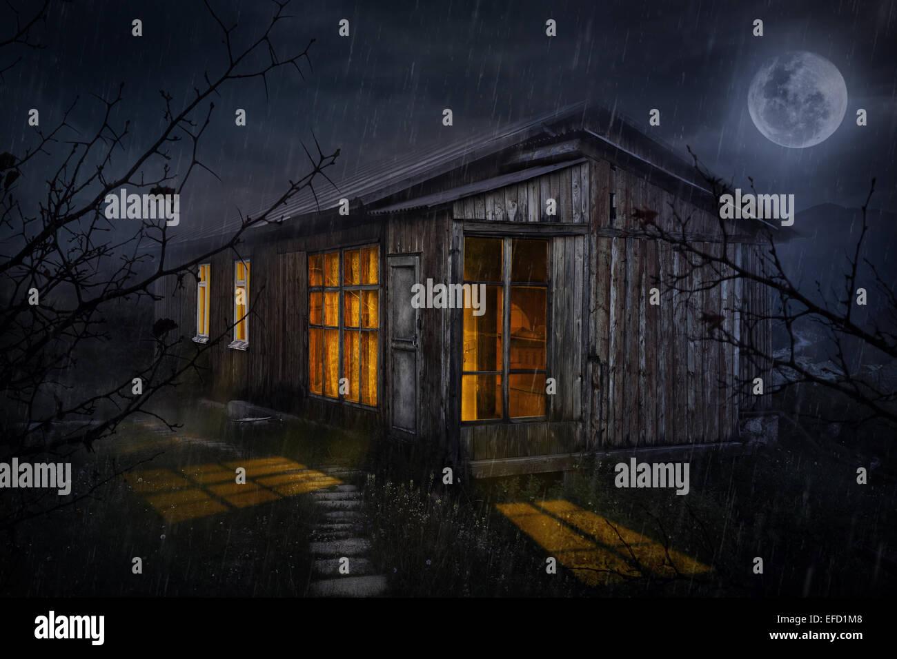 Casa rural con sus resplandecientes ventanas en el cielo nocturno con luna Imagen De Stock