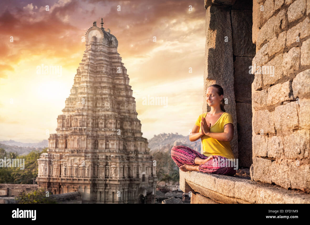 Mujer con Namaste mudra sentados cerca de templo Virupaksha en Hampi, Karnataka, India Imagen De Stock