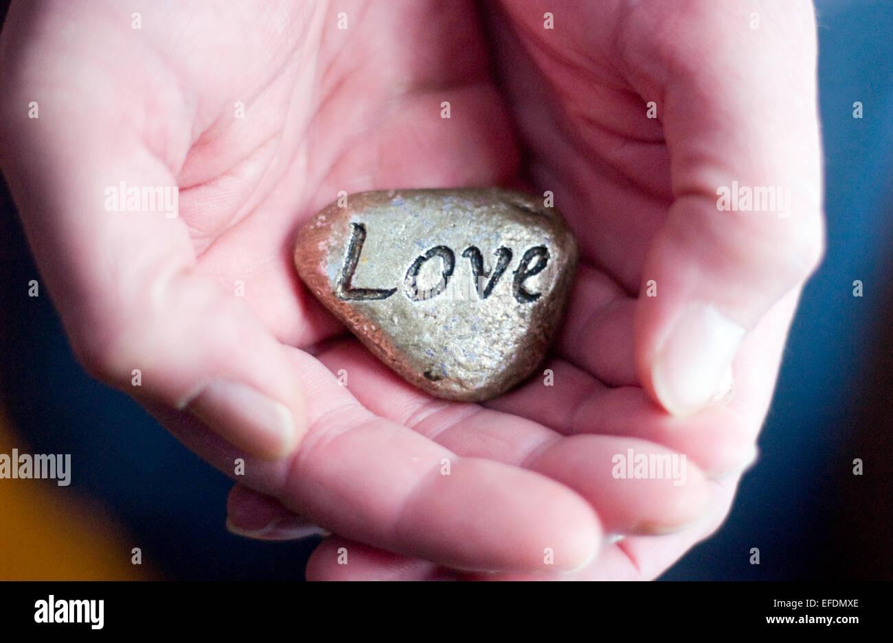 Mano sujetando la piedra del amor. Amor y cuidado concepto Imagen De Stock
