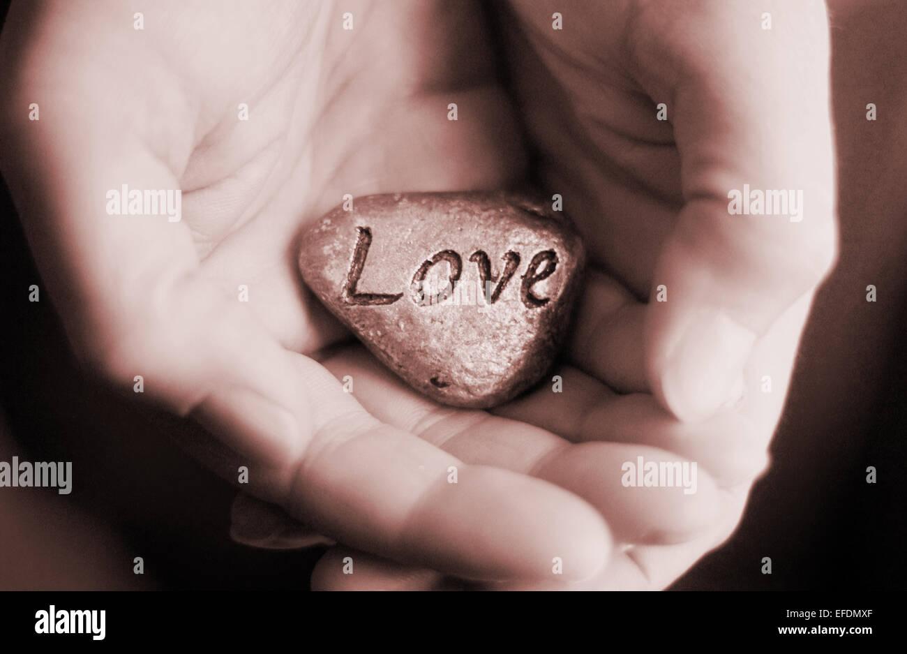 Mano sujetando la piedra del amor. Amor y cuidado concepto Foto de stock