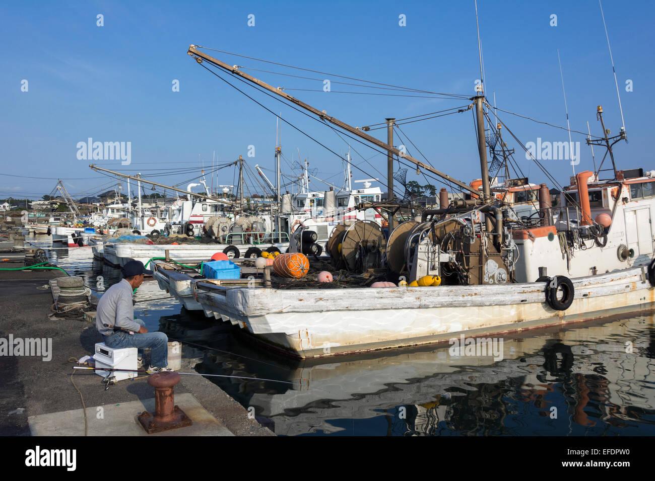 Hombre que pesca el modo low tech junto a algunos barcos de pesca de alta tecnología, Naruto Harbour, la isla Imagen De Stock
