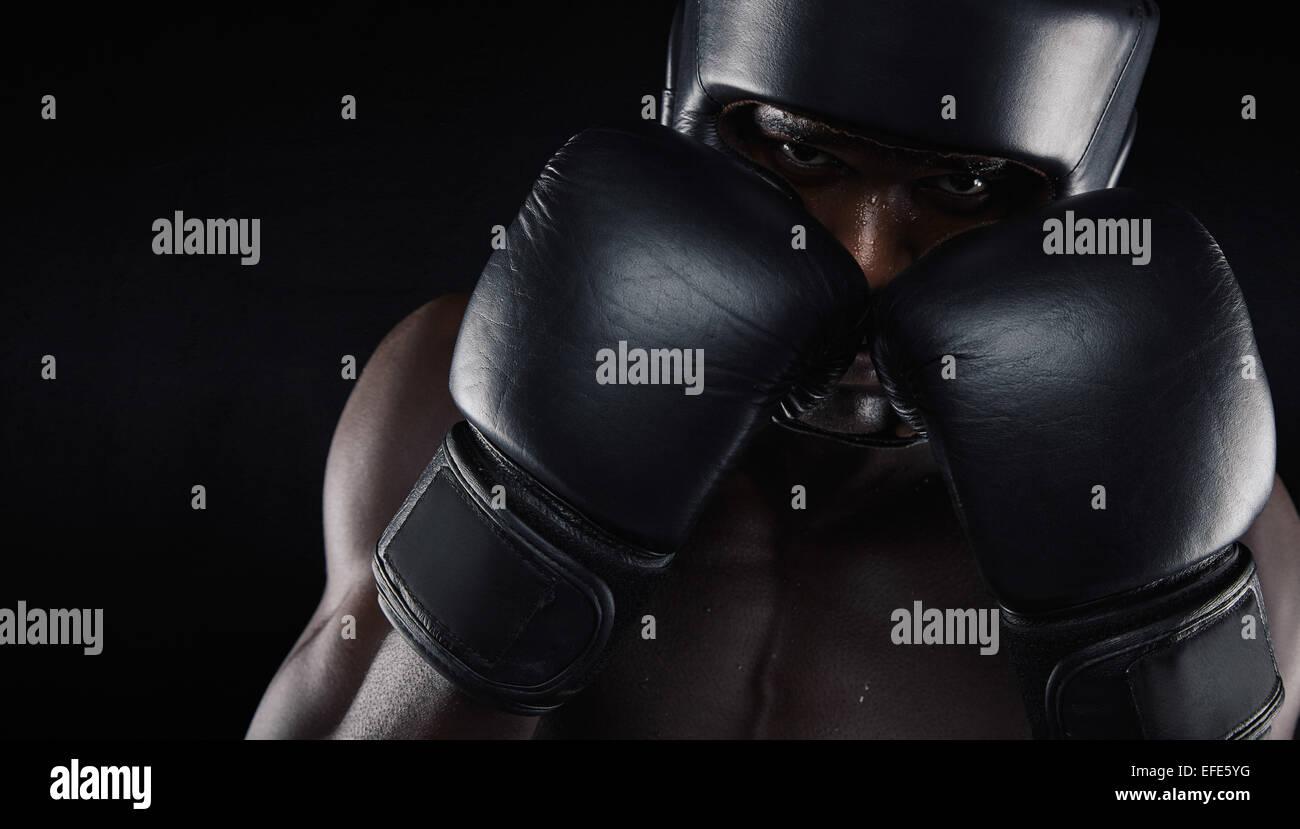 Boxeador afroamericano vistiendo ropa protectora contra el fondo negro. Joven el ejercicio de boxeo. Imagen De Stock