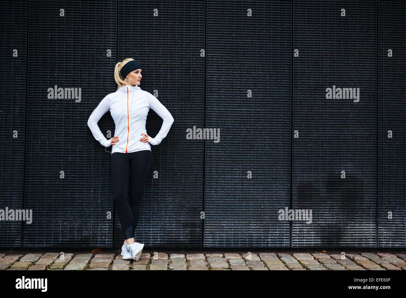 Determinada mujer descansando después de correr en la ciudad. Longitud total de filmación joven deportivo Imagen De Stock