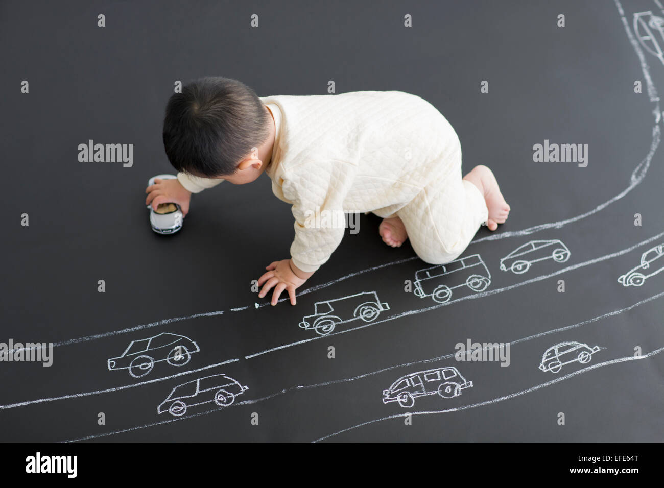 Lindo bebé jugando con coches de juguete en el tablero de dibujo Imagen De Stock