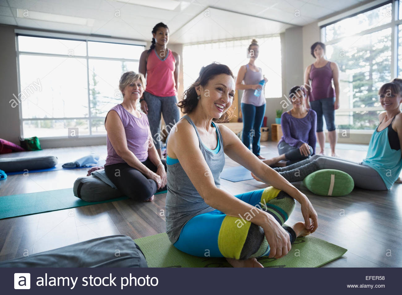 Mujer sonriente en clase de yoga restaurador Imagen De Stock