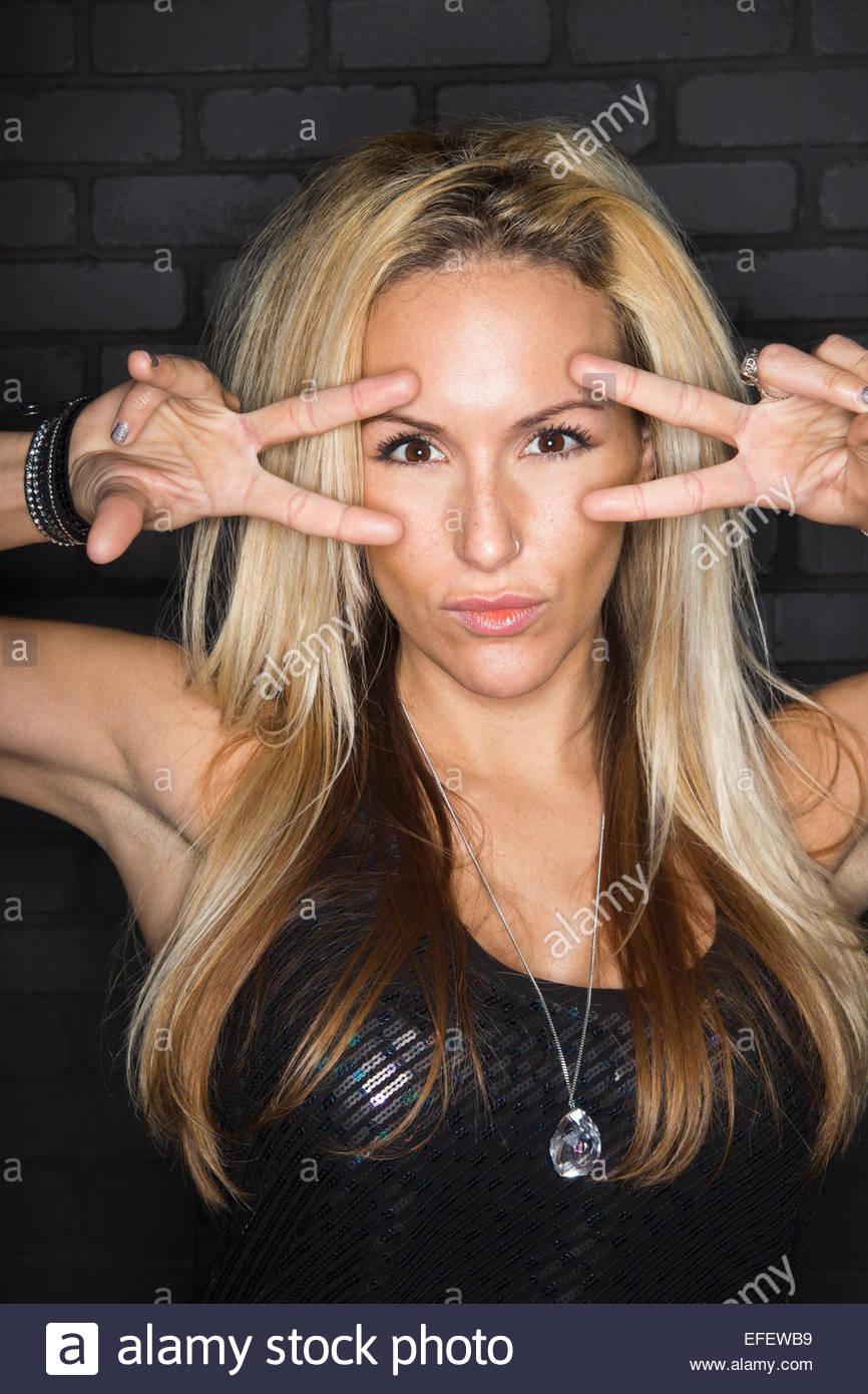 Retrato de cool mujer rubia gesticula signo de paz Imagen De Stock