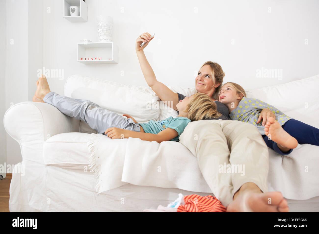 Madre, hija e hijo en el sofá tomando un selfie Foto de stock
