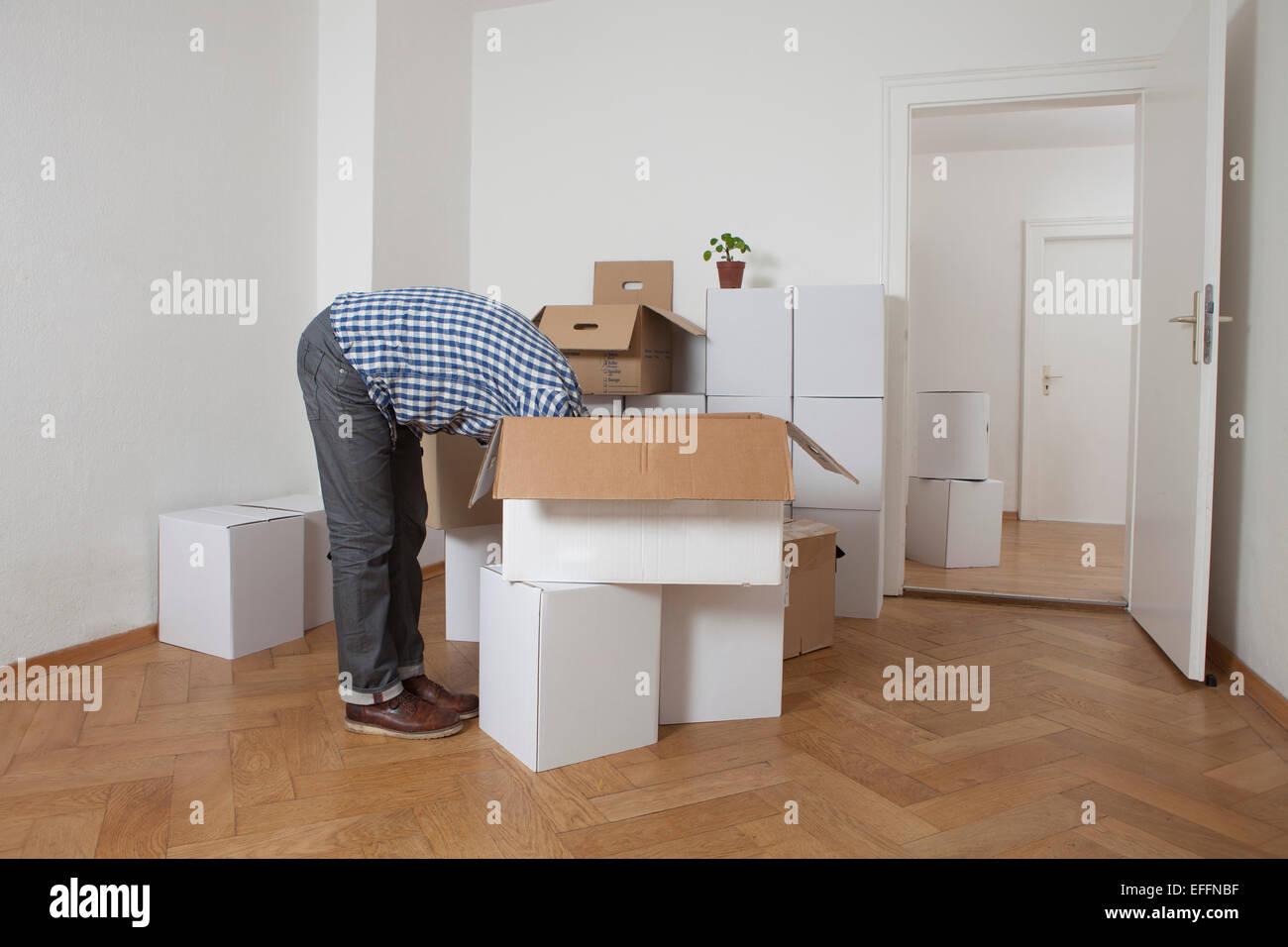 El hombre busca la cabeza primero en caja de cartón Imagen De Stock