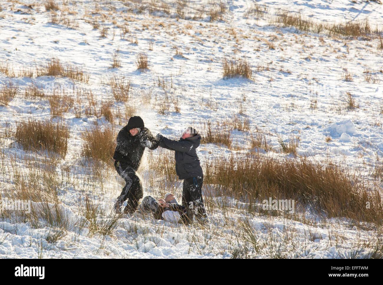 Los niños tienen una lucha de bolas de nieve sobre Kirkstone Pass en nieve, Lake District, RU Imagen De Stock