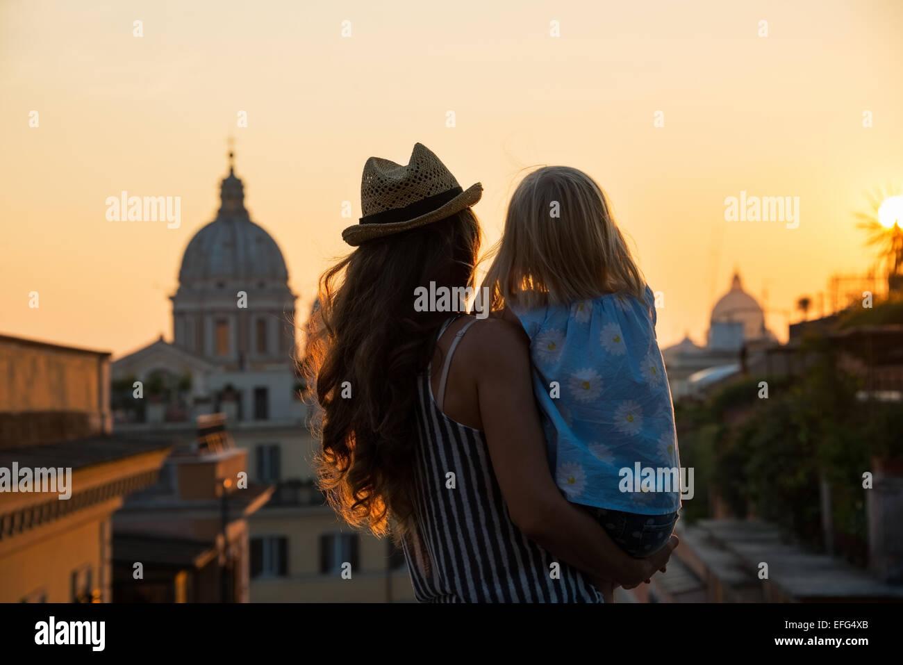 Silueta de la madre y el bebé niña mirando sobre los tejados de Roma vista posterior a la puesta del sol. Foto de stock
