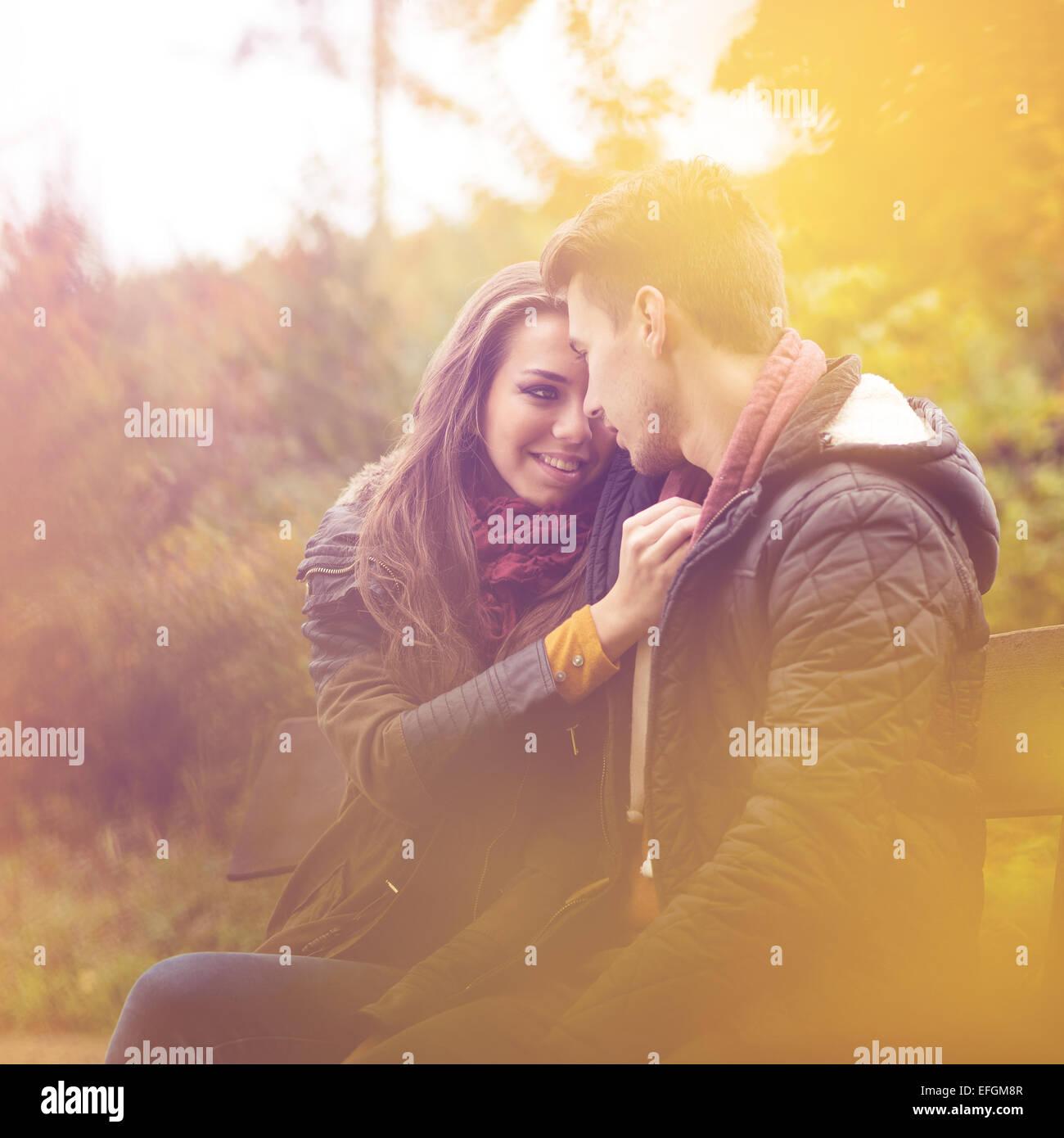 Par de otoño colorido bosque, sentados en un banco Foto de stock