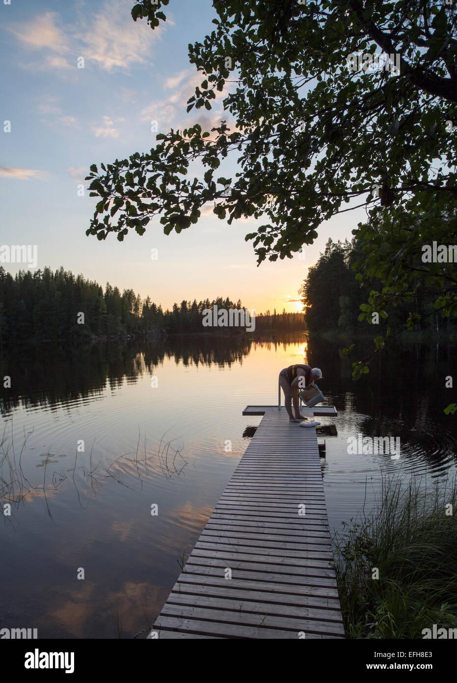 Anciana va a nadar a un pequeño lago en el campo al atardecer , Finlandia Foto de stock