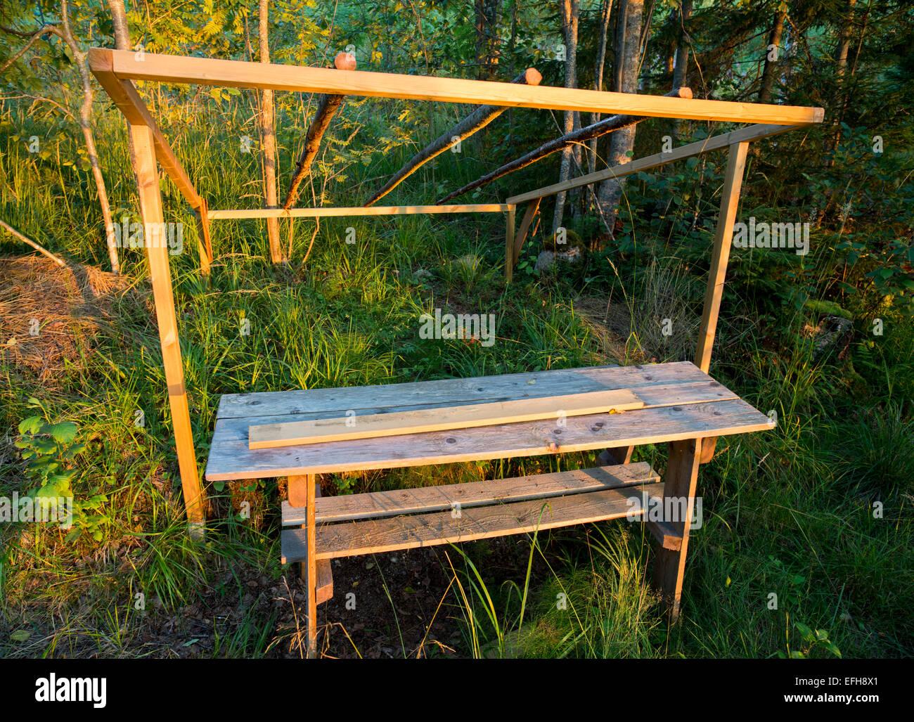 Mesas y sillas de madera rudimentarias y el bastidor para hacer un abrigo impermeable Foto de stock