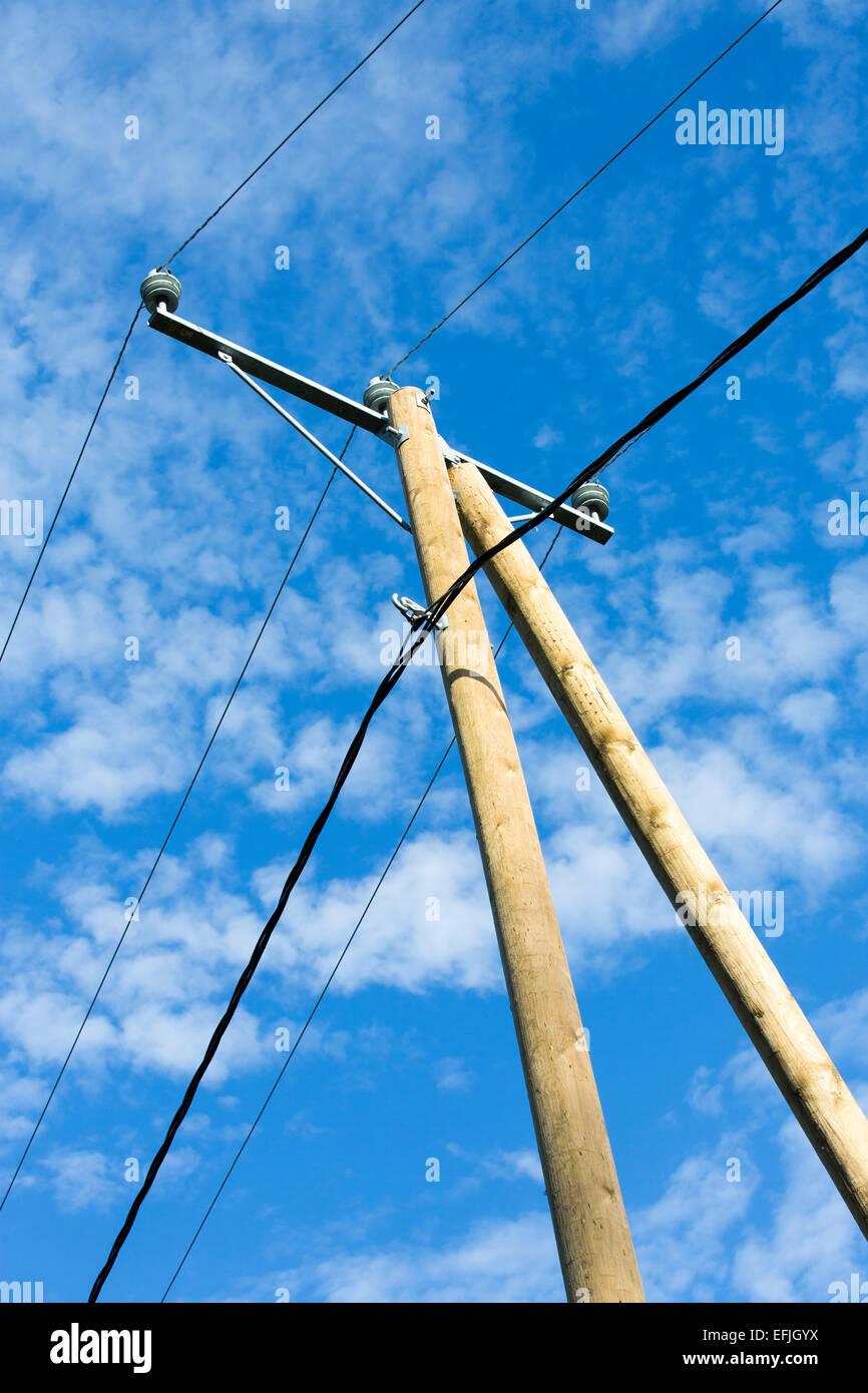 Nueva utilidad de madera polo con cables de línea de alimentación y apoyo contra el cielo azul Foto de stock